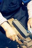Craftsman sharpen scissor with whetstone — Stock Photo