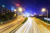 Traffic blur motion trails in modern city street at night — Stock Photo