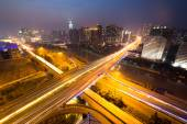 Traffic light trails on overpass and cityscape — Stock Photo