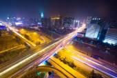 Senderos de luz de tráfico en puente y paisaje urbano — Foto de Stock