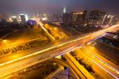 Traffic light trails on overpass and cityscape — Foto de Stock