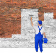 House painter covers brick wall with white paint — Stock Photo #59993851