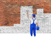 House painter covers brick wall with white paint — Stock Photo