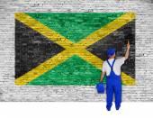 Anstreicher deckt Ziegelmauer mit Flagge von Jamaika — Stockfoto