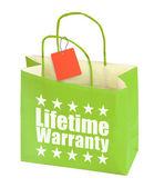 Paper bag with lifetime warranty inscription — Stock Photo