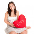Cute young woman holding red heart pillow — Stock Photo #59504355