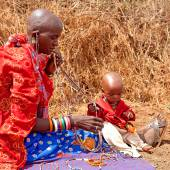 Masai woman with child is showing traditional jewelry — Stock Photo
