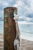 Wooden post with rope handrails on a pier — Photo