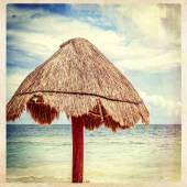 Grass palapa umbrella on beach — Stock Photo