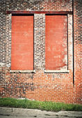 Two windows in a brick building boarded up with cinder blocks — Stock Photo