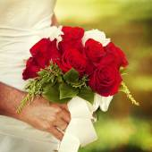 Bride holding red rose bouquet — Stock Photo