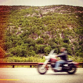 Motorcyclist speeding by on a mountain road — Stock Photo