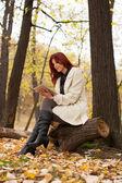 Ung kvinna med tablett på bänken — Stockfoto