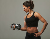 Sexy athletic woman pumping up muscles with dumbbells — Stock fotografie