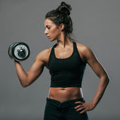 Sexy athletic woman pumping up muscles with dumbbells — Stock Photo