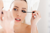 Young woman looking in the mirror and putting make-up on. Preparing for busy day. — Stock Photo