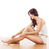 Image of smiling young women, depilating legs. — Stockfoto
