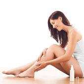 Woman sitting on the floor and apply body lotion on the leg skin.Studio shot — Stockfoto