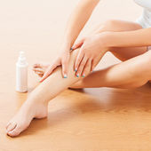 Woman sitting on the floor and apply body lotion on the leg skin.Studio shot — Foto de Stock