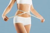 Beautiful female figure,women holding a meter around hip.Healthy lifestyles concept — Stockfoto