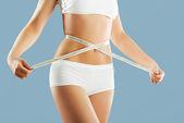 Beautiful female figure,women holding a meter around hip.Healthy lifestyles concept — Foto de Stock