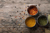 Overhead view of Colourful dried ground spices in bowls on old aged scored wooden surface in a country kitchen — Stock Photo