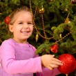 Adorable toddler girl holding decorative Christmas toy ball — Stock Photo #58943701