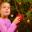 Adorable toddler girl holding decorative Christmas toy ball — Stock Photo #58943717