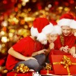 Christmas Kids Opening Present Gift Box, Happy Children in Santa Hat, Smiling Boys and Girls In Red Cap Funny Looking Toys — Fotografia Stock  #57375303