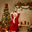 Christmas Kid Boy In Santa Hat And Bag, Child Happy Celebrate New Year, Room Decorated by Xmas Tree Present Gift Boxes and Candles — Zdjęcie stockowe #57639125
