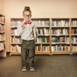 School Kid in Library, Child in Glasses with Book, Girl Student Bookcase Shelves — Stock Photo #71540961