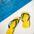 Old sandals by the pool — Stock Photo #65897133