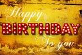 Glowing birthday greetings over distressed yellow paint — Foto Stock