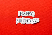 Red Happy birthday on scrap of paper — Stock Photo