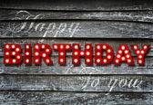 Glowing Happy Birthday on wooden background — Stockfoto