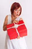 Excited  red headed woman opening a present — Stock Photo