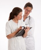 Doctor and nurse looking to a medical history — Stock Photo