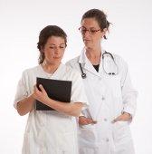 Doctor and nurse examining a file — Stockfoto