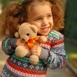 Girl in park hugging a teddy bear — Stock Photo #53973225