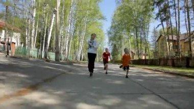 Active mother with her children running outdoor in spring — Stock Video