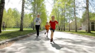 Mother and two boys running outdoor in spring — Stock Video