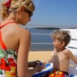 Happy mother applying sunscreen on the face and body of little kid — Stock Video #76567105