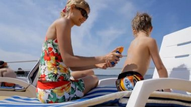 Young beautiful mother applying sunscreen on son's back — Stock Video