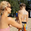 Young woman applying sun block on the back of little boy on the beach. — Stock Video #76863649