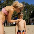 Mother and son applying sun screen lotion on the beach. Healthy sunbathing. — Stock Video #76865561