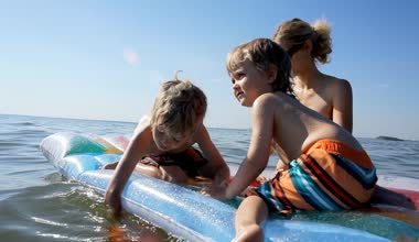Mother with two kids swim in sea, boys sitting on inflatable mattress — Stock Video
