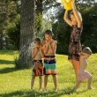Mom pours water from a watering can on happy children in green park. — Stock Video #78753478