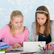 Two teen girls making homework together with digital tablet — Stock Photo #61539609