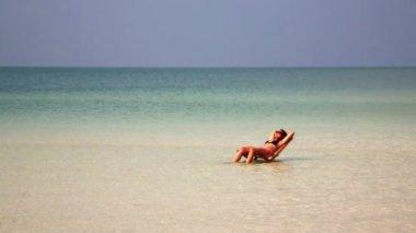 Woman sunbathing in crystal water — Stock Video