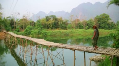 Tourist girl walking on bamboo bridge — Stock Video